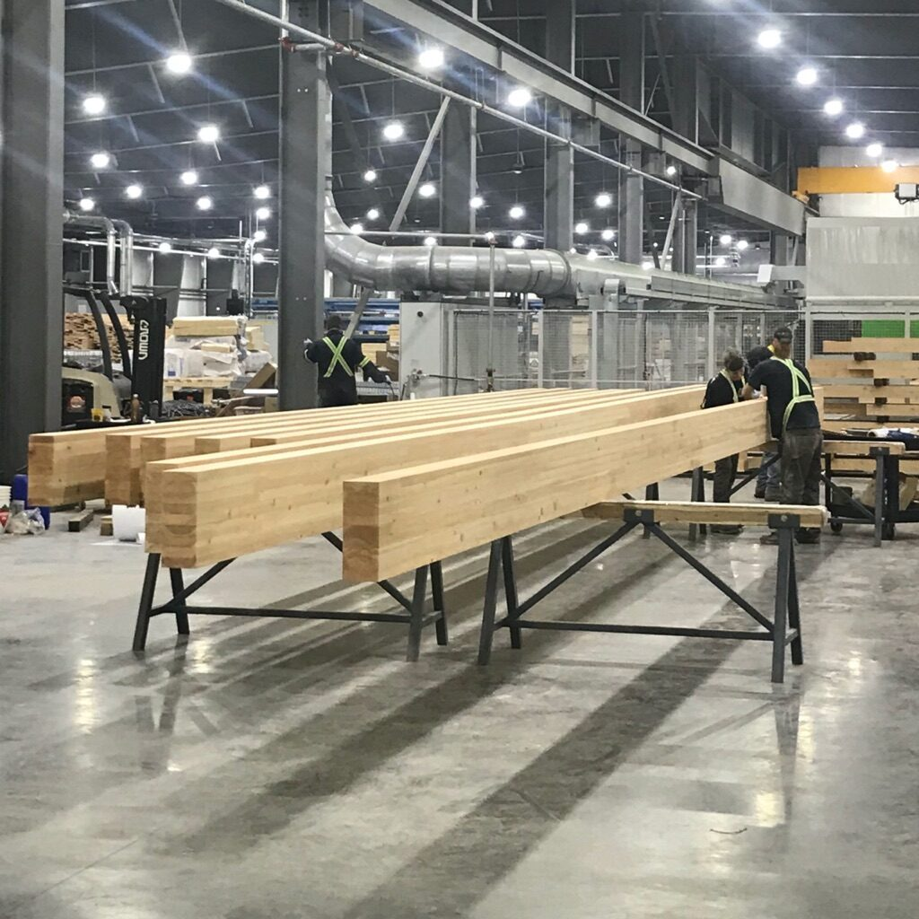 eight mass timber glulam beams being scaled by facility engineers
