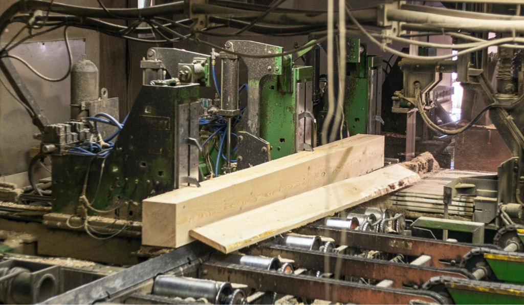 softwood lumber in timber sawmill getting cut into a structural wood beam