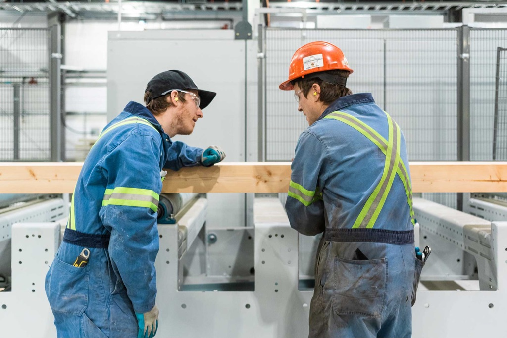 two mass timber engineers discussing cross laminated beam on production line