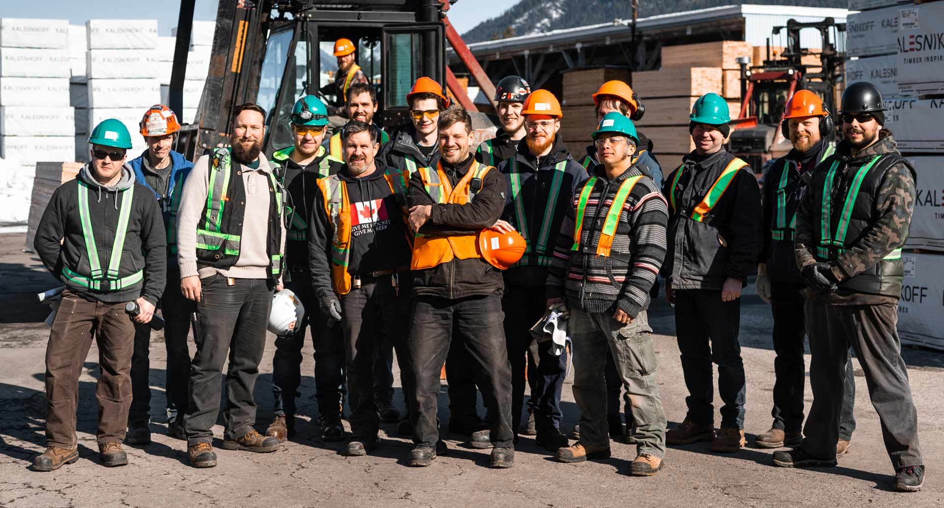 Kalesnikoff team of mass timber engineers and specialists in front of palettes of lumber