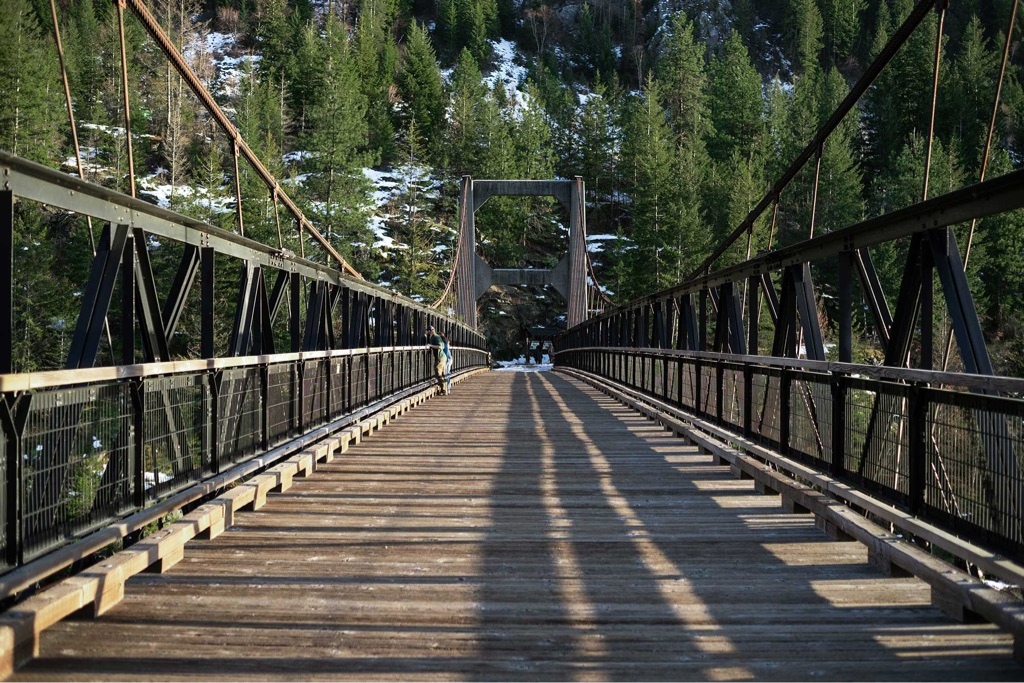 start of suspension bridge leading to forested mountain with snow on the ground